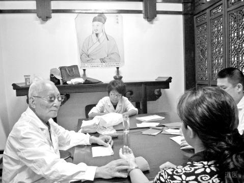 颜正华(左一)为患者看病、带教
